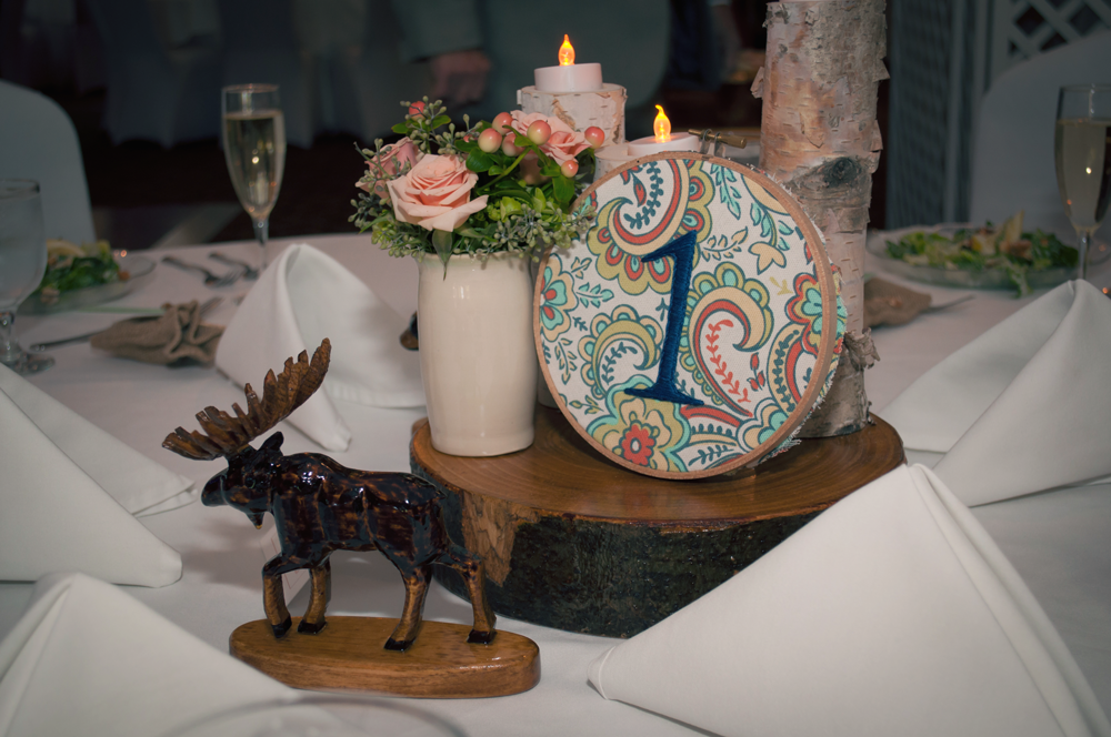 Each table number was cross-stitched by Katie (the bride), the vases were made by the mother of the bride, and the wooden centerpieces and figurines were made by the father of the bride.