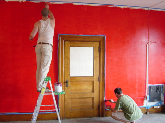 painters painting red wall
