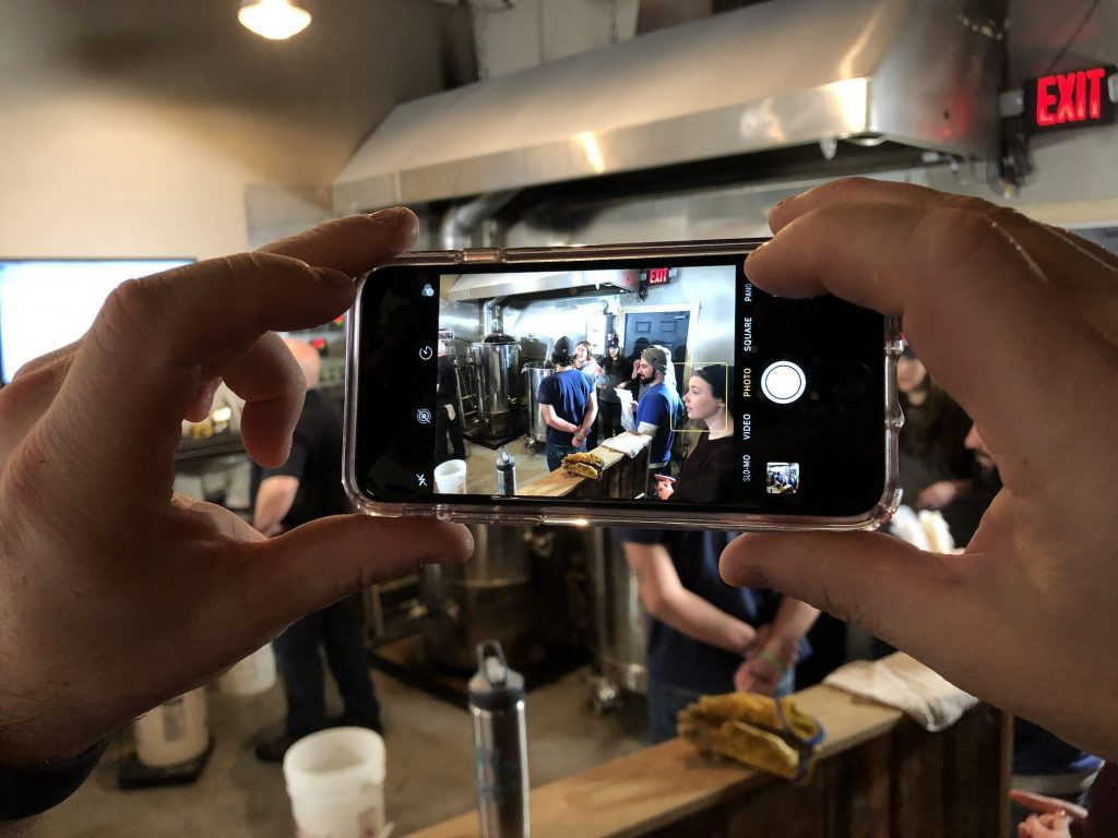 An iPhone screen showing people in a brewing facility.
