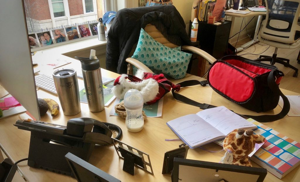 Work space with personal items, a baby bottle, documents, and food.