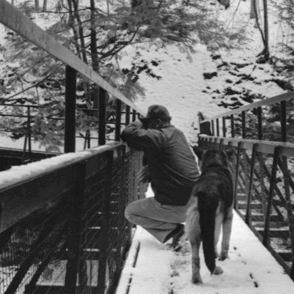 Man with dog on bridge in winter