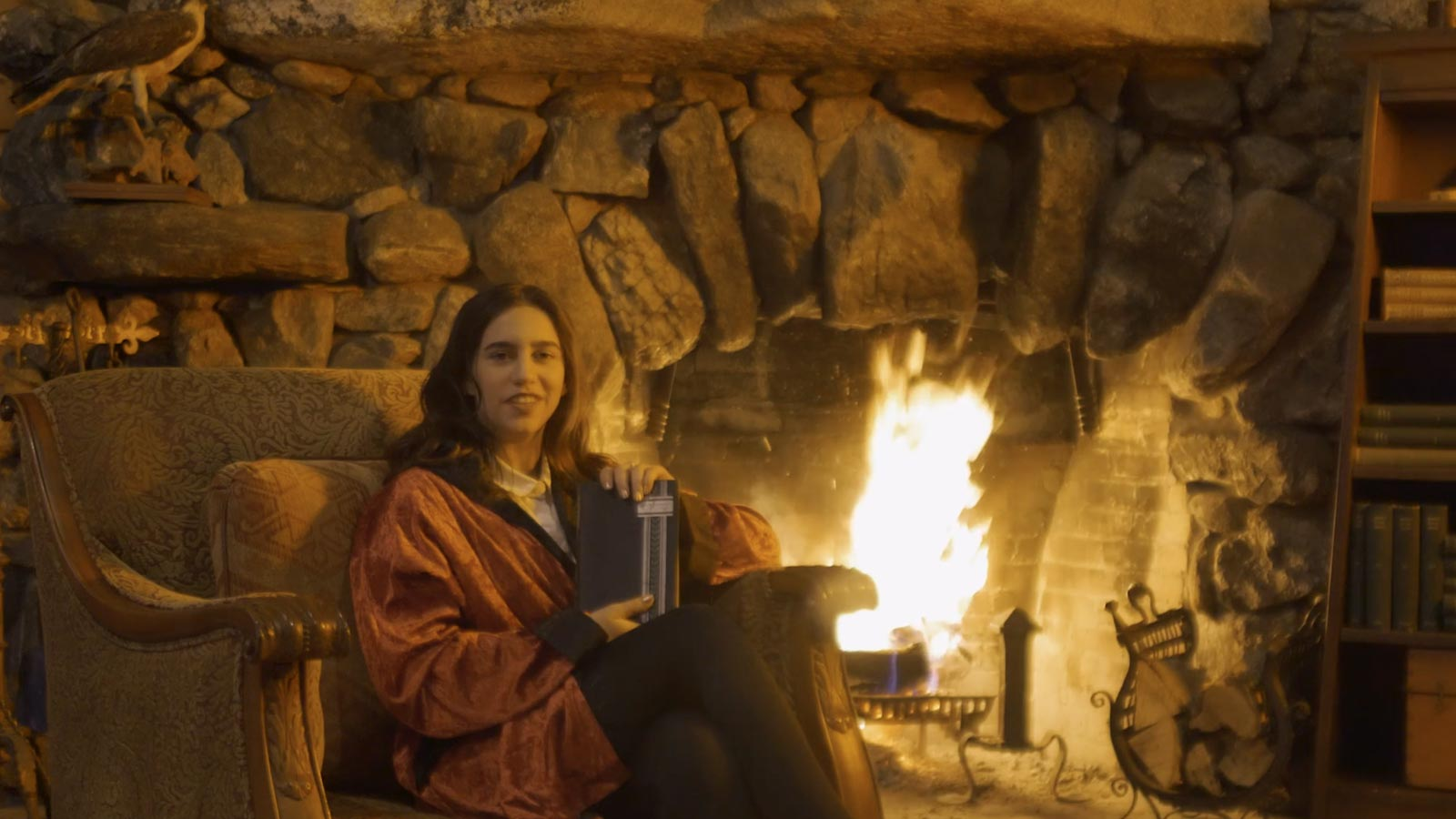 Women in front of fireplace with book