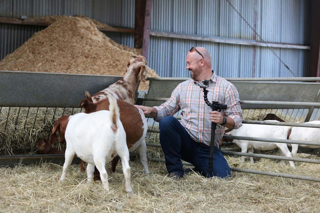 A photographer crouches and laughs as he pets the head of a flirtatious goat.