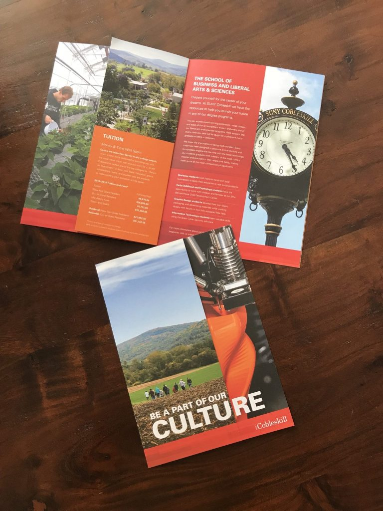 Two brochures for SUNY Cobleskill sit on a dark wood table. They have photographic images of a clock tower and a cow pasture.