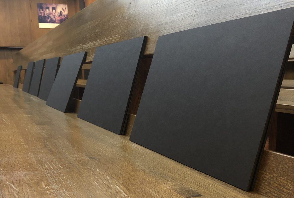 The backside of presentation boards face out from a long wooden bench before a presentation.