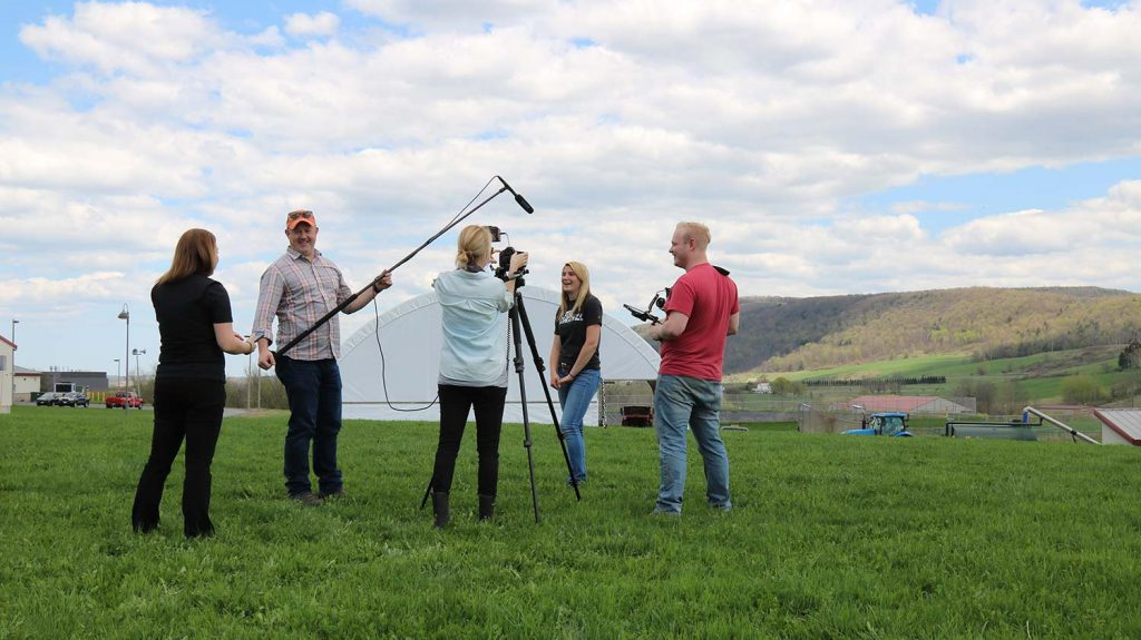 An active video shoot on the SUNY Cobleskill campus. The sky is wide and blue overhead, two photographers stand on the bright green grass while another crew members holds a boom mic toward a blonde female student being interviewed.