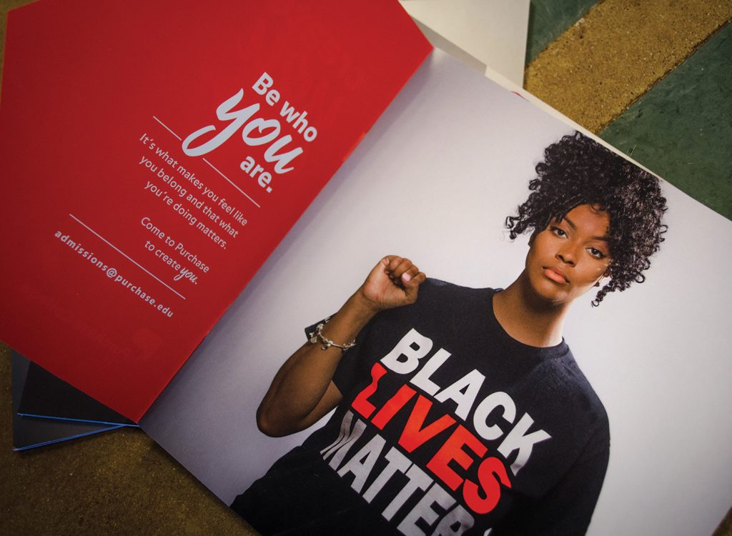 A young black woman faces the camera wearing a black t-shirt with the BLACK LIVES MATTER written in bold red and white letters.