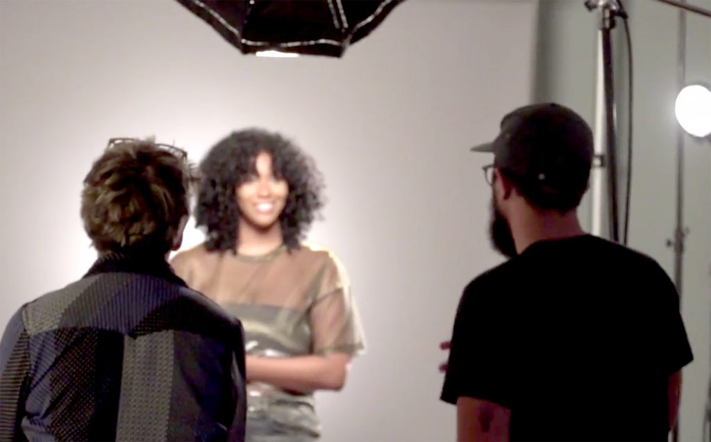 An African American woman can be seen in front of cameras and lights through the back of a man and woman.