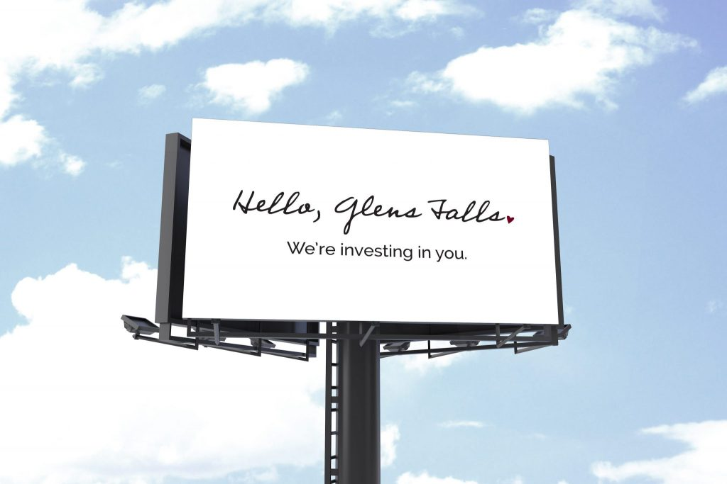 "A stark billboard against a blue sky, reading a in cursive font, ""Hello, Glens Falls. We're investing oin you."""