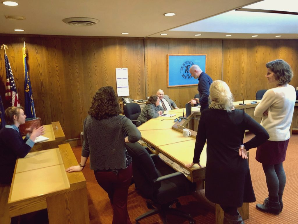 A group f of people gathered in a wood paneled conference room to review a presentation.