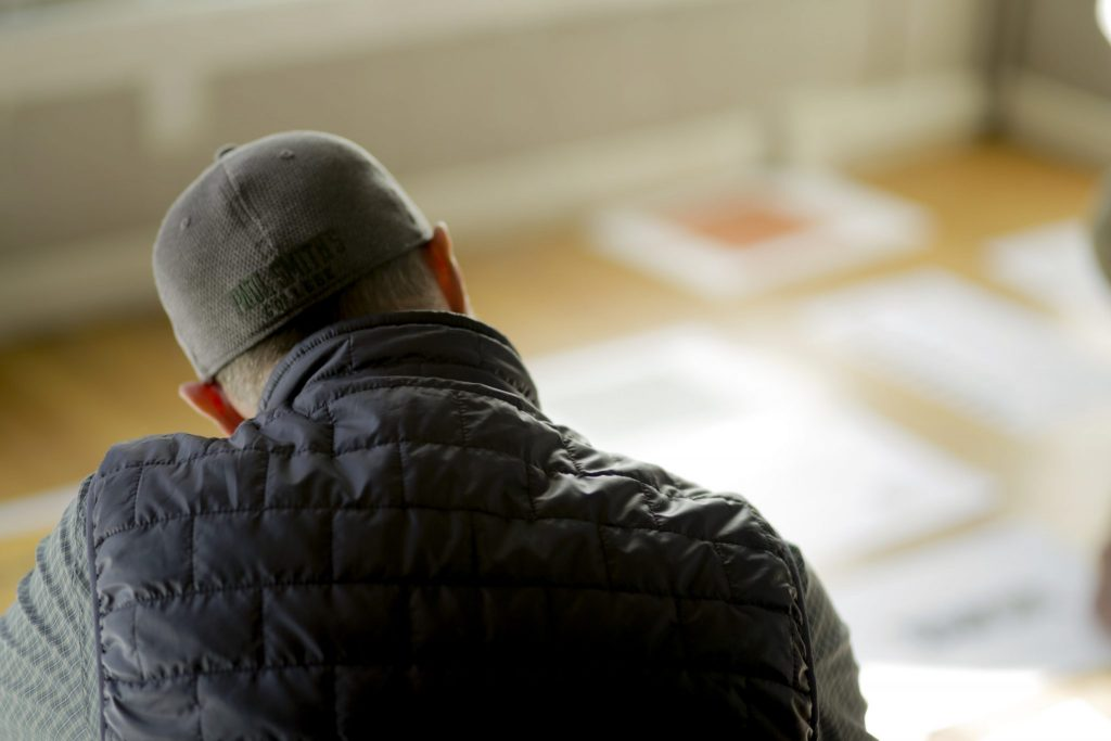 A man can be seen looking over sheets of paper placed on a hardwood floor. He is wearing a ball cap and jacket. Sunlight pours through the windows onto the papers.