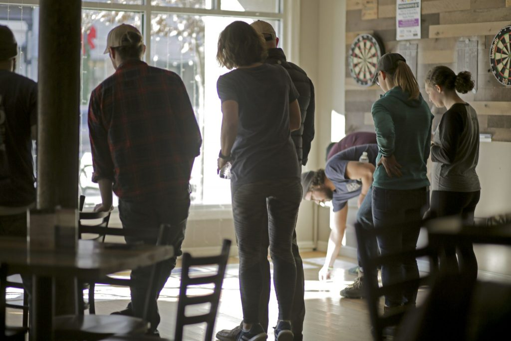 A group is gathered in a half cirlcle reviewing sheets of paper on the floor.