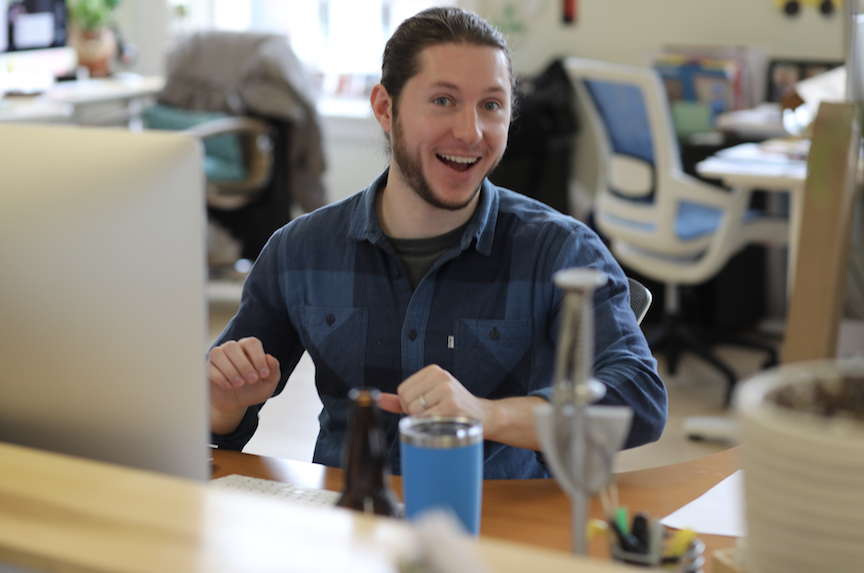 A man with a beard and man bun smiles at the camera as he sits in an office environment.