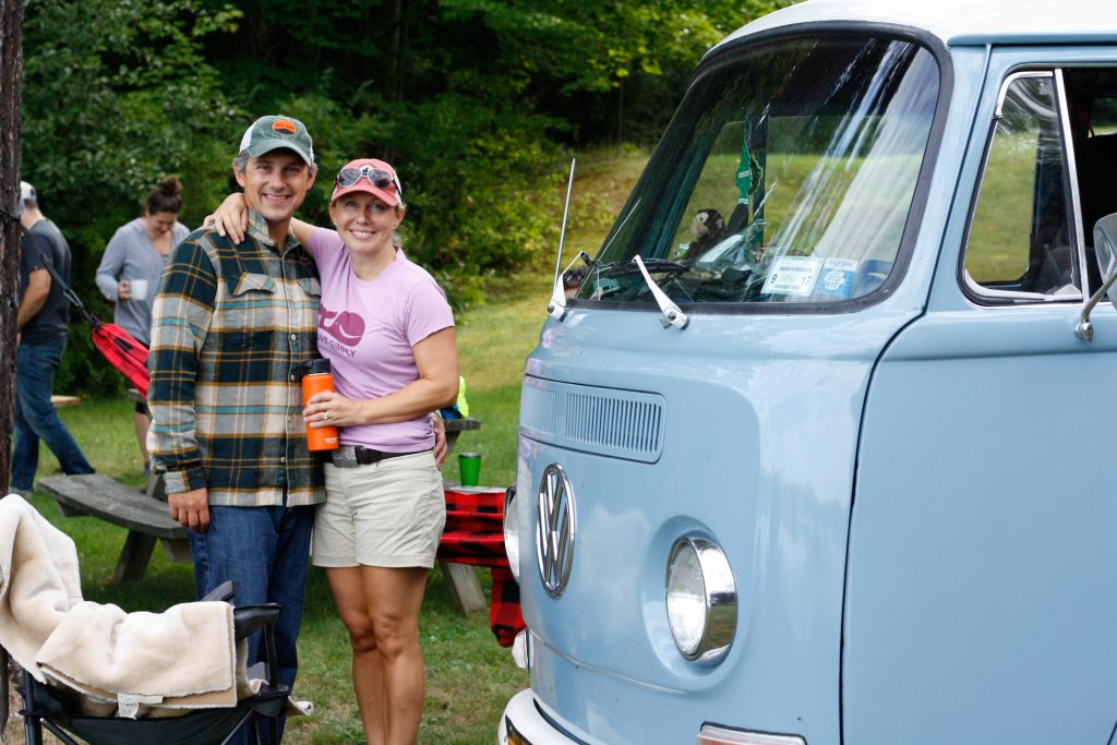 Showcasing the outdoor lifestyle with people in caps and flannels standing next to a VW bus.