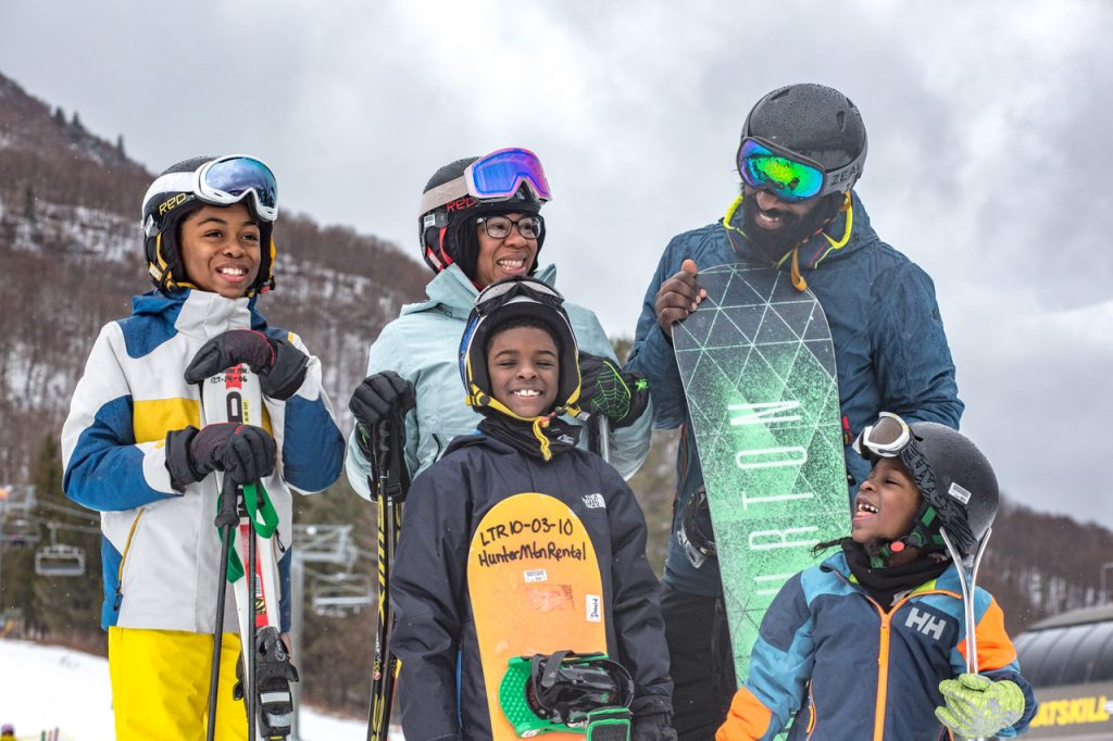 A black family-two parents and three children, stand at the base of a mountain in ski and snowboarding gear.