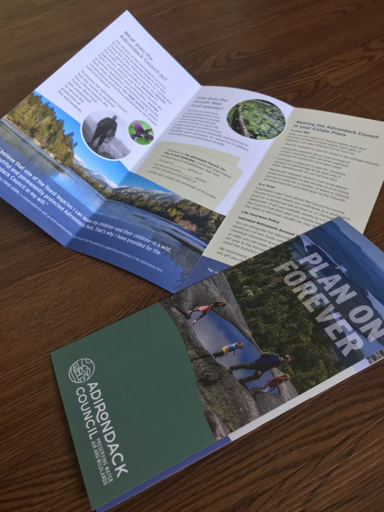 Two brochures presented on a wood background.