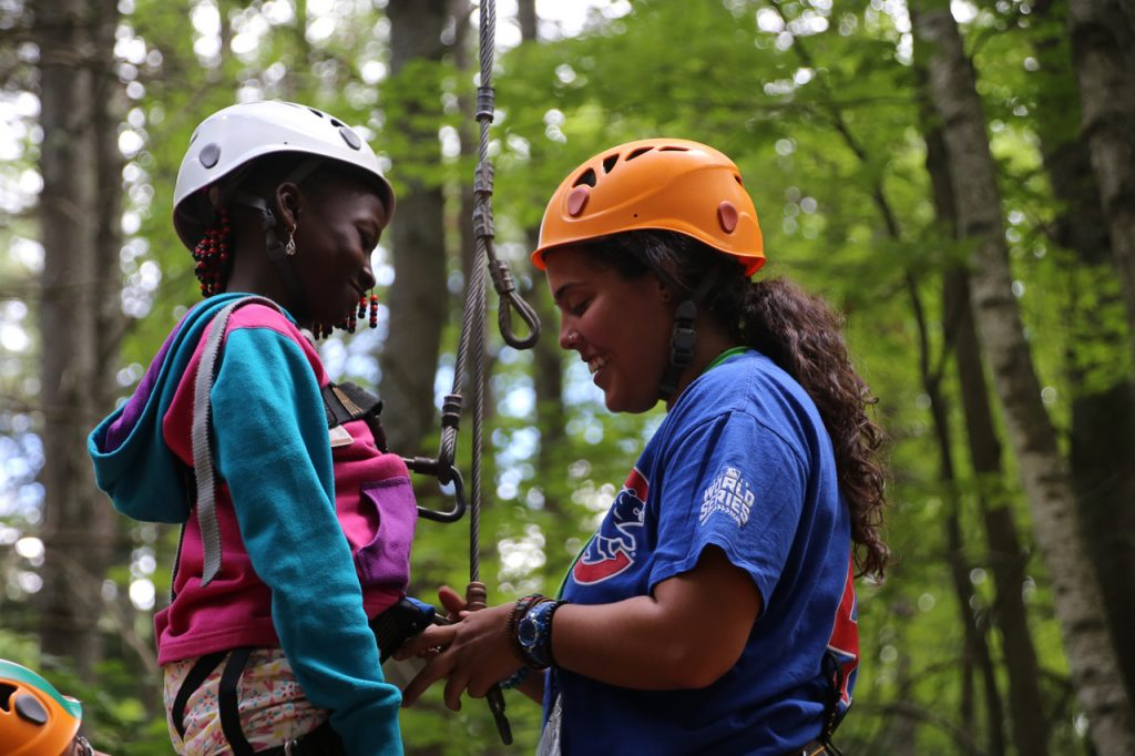 A young black girls has a climbing harness put on her by a college-age counselor.
