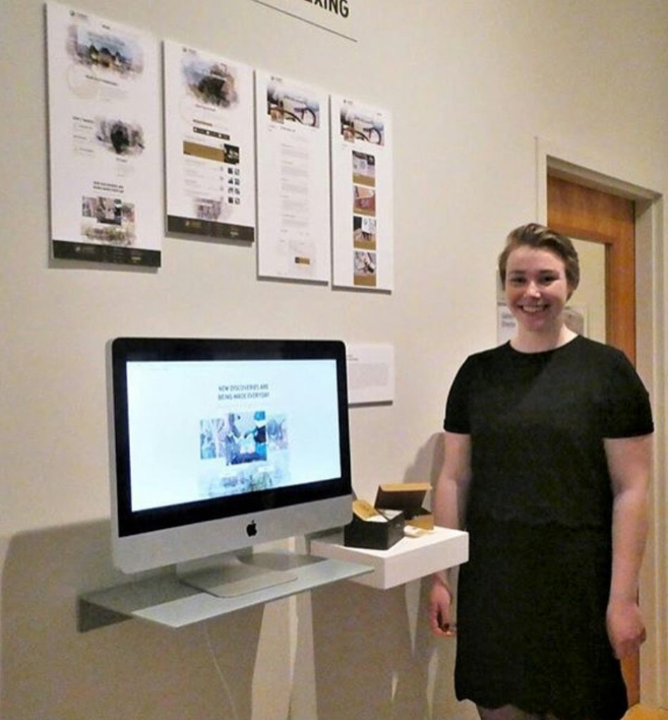 A young woman stands in front of her senior project.