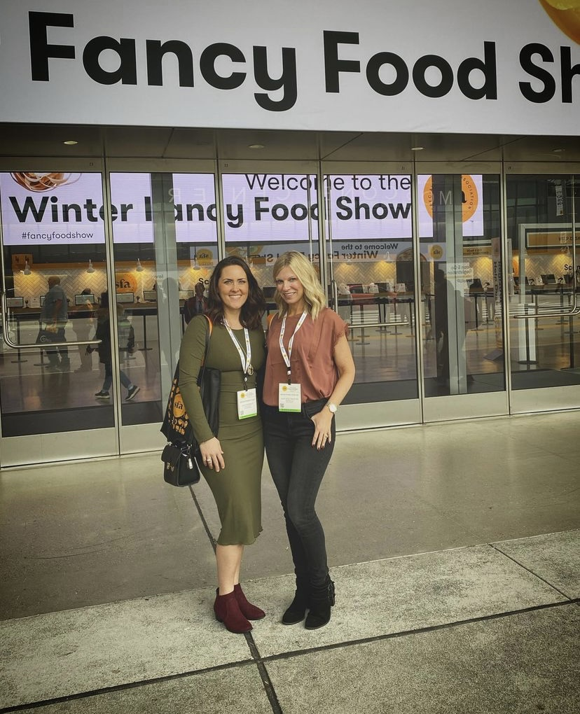 Two women with conference lanyards stand outside of a trade show for the Fancy Food Show.