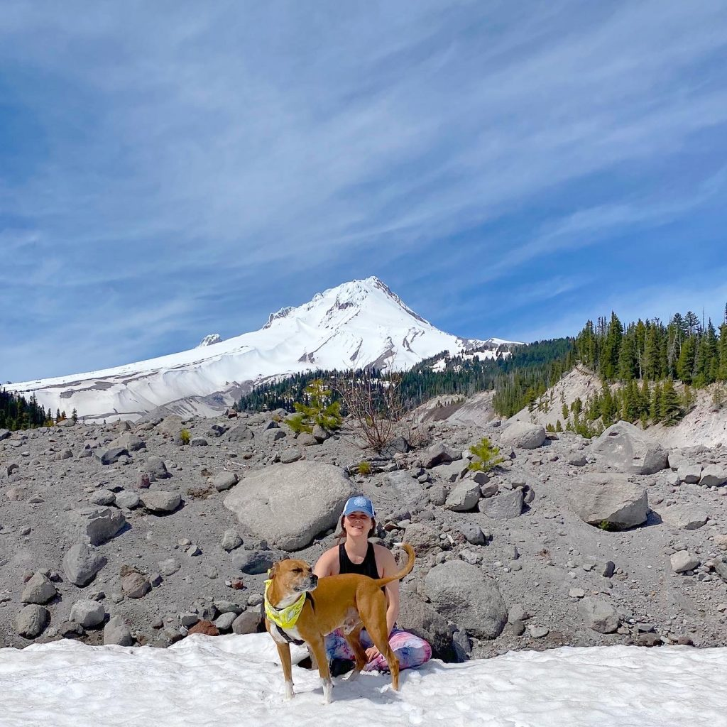 A woman sits with a dog wearing. bandana infant of a snow covered Mount Hood.